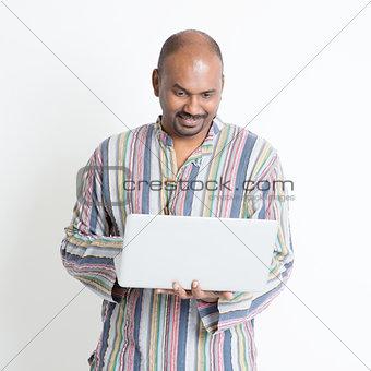 Mature casual Indian man using laptop computer