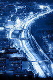Night road with motion traffic in the city, blue