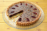 Pecan pie on a plate with one slice taken