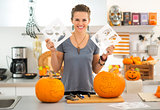 Woman with Halloween carving patterns preparing for party