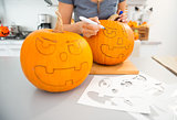 Woman creating pumpkins Jack-O-Lante for Halloween. Closeup