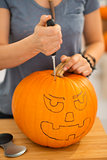Woman carving pumpkin for Halloween party. Closeup