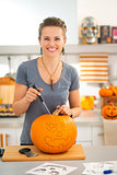 Woman carving pumpkin Jack-O-Lantern for Halloween party