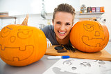 Funny young woman creating pumpkins for Halloween party