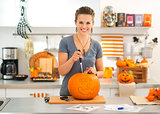 Young woman carving a pumpkin Jack-O-Lantern for Halloween party