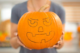 Closeup. big scary Halloween pumpkin Jack-O-Lantern in woman's h