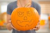 Closeup. big scary Halloween pumpkin Jack-O-Lantern in woman's h