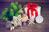 Christmas still life with fir gift and tinsel on wooden board