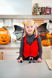 Interested girl in halloween bat costume in kitchen