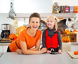 Funny girl in halloween bat costume with mother in kitchen