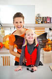Happy girl in halloween bat costume with mother in kitchen
