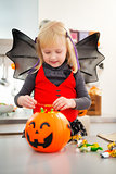 Interested girl in halloween bat costume checking candy