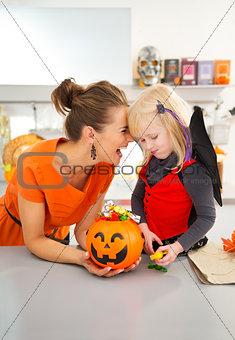 Portrait of happy mother with daughter in halloween bat costume