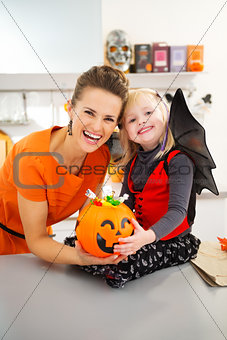 Portrait of halloween dressed girl with mother and candy