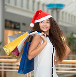 Christmas shopping, girl holding colorful shopping bags wearing santa hat