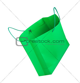 green shopping bag falling through the air on an isolated white