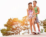 Young happy couple with a skateboard
