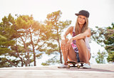 Young woman sitting on a skateboard outdoors