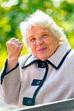 gray-haired old lady shows a fist in the park