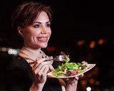 Happy woman eating salad