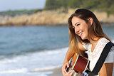 Beautiful guitarist woman playing guitar on the beach