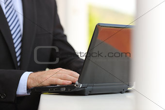 Business man hand using a laptop in the street