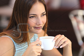 Candid woman thinking in a coffee shop