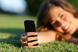 Close up of a happy teen girl hand using a smart phone on the grass