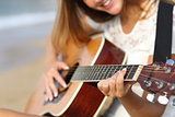 Close up of a woman playing guitar on the beach