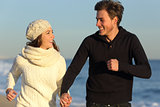 Couple running on the beach in winter