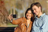 Couple taking selfie photo sitting in a bench