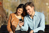Couple watching a smart phone sitting on a bench