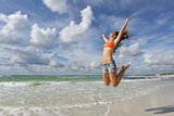 Happy girl jumping on the beach on holidays