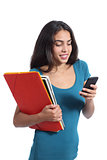 Happy student teen holding books and texting on a smart phone