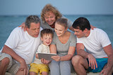 Happy big family with tablet PC on the beach