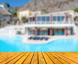 Wood table in perspective. Blurred hotel with pool and mountains view