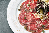 Carpaccio with olives and Parmesan on plate