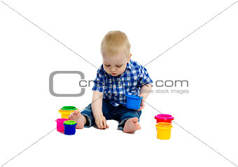 little boy in checkered shirt plays on the floor. Studio