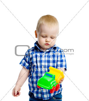 little boy in checkered shirt plays with a toy car