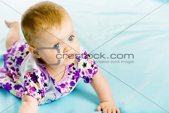 baby girl in a dress creeps on the blue coverlet