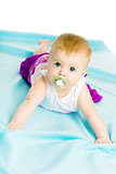 baby girl with pacifier crawling on the blue coverlet