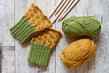 wool green and yellow legwarmers, knitting needles and yarn