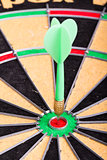 green Dart hitting the dartboard