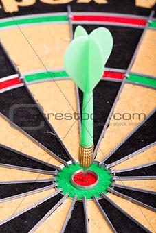 green Dart hitting the dartboard