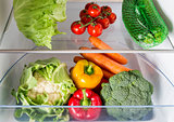 Open fridge filled with fruits and vegetables