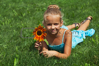 Little girl laying on the grass with a flower