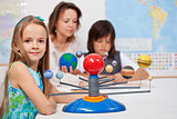Kids study the solar system under their teacher supervision