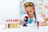 Little girl in science class using microscope