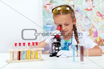 Little girl in science class using microscope