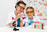 Teacher showing basic chemistry experiment to a little student